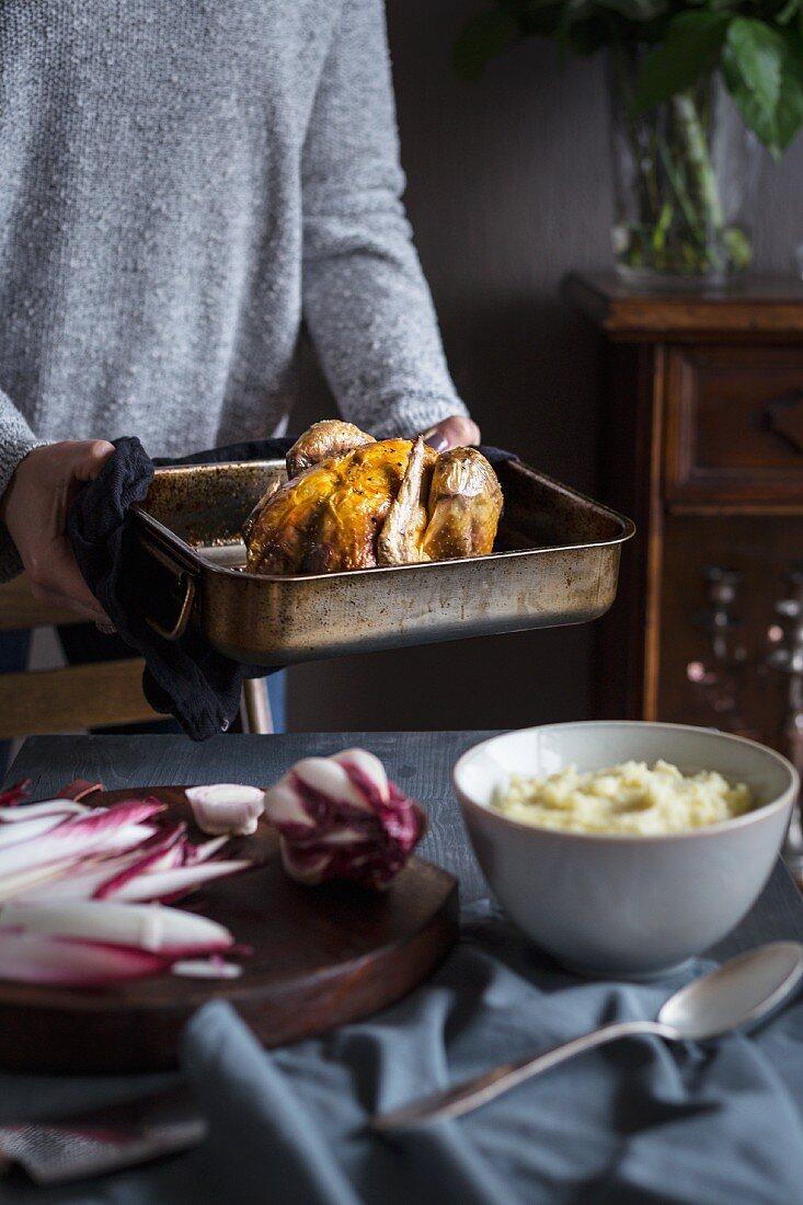 Woman serving roast chicken in pure