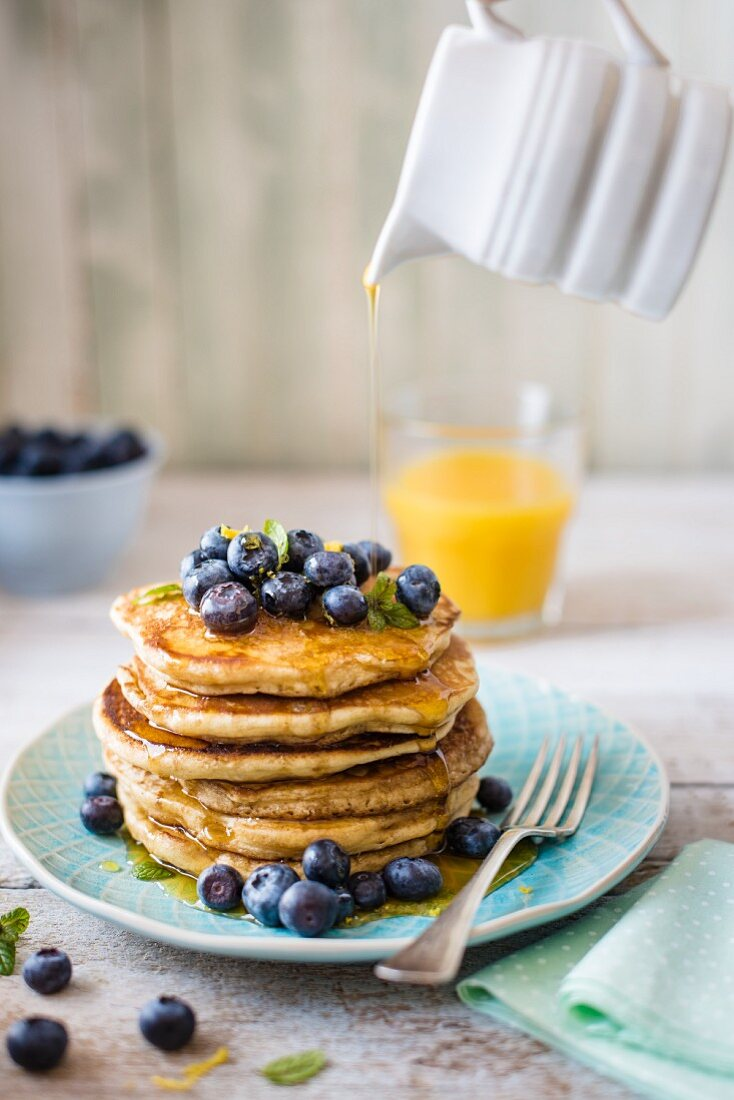 Sstack of pancakes with lemon zest, bueberries and maple syrup for breakfast