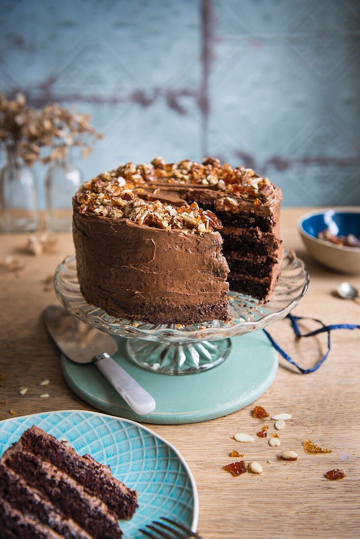 Chocolate almond cake with brittle topping on a cake stand with a slice removed