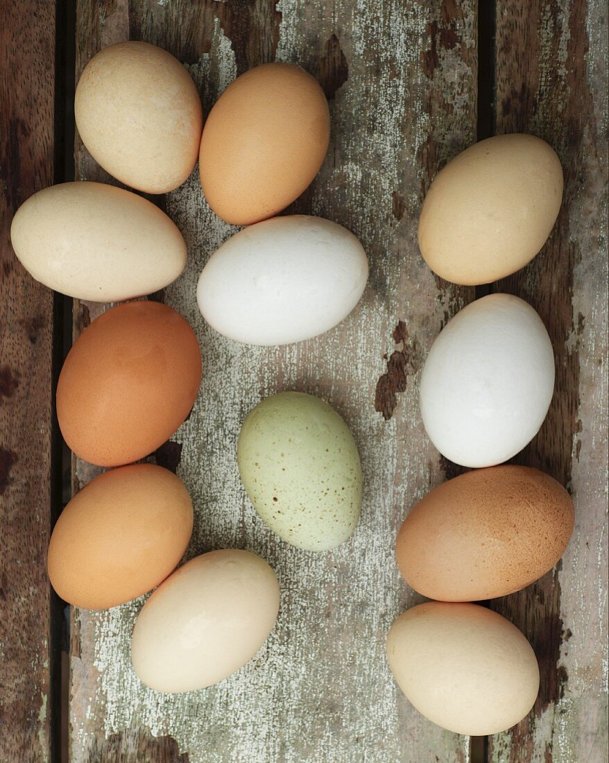 Different-coloured fresh eggs on a wooden background