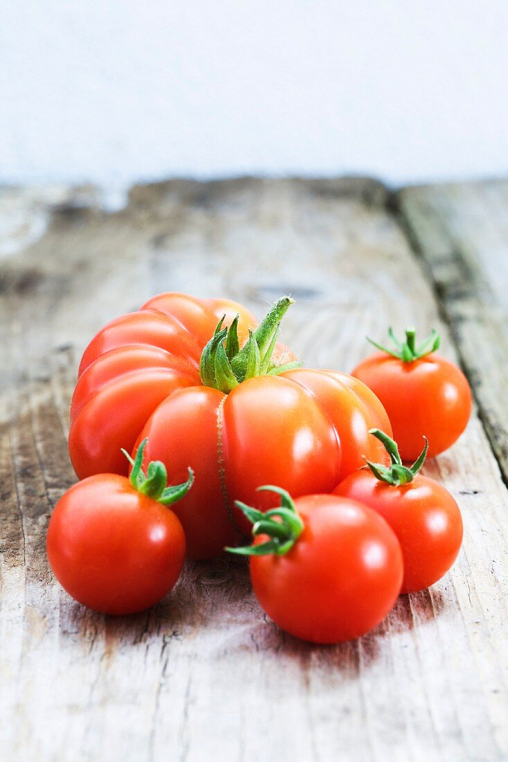 Various types of tomatoes on wooden background