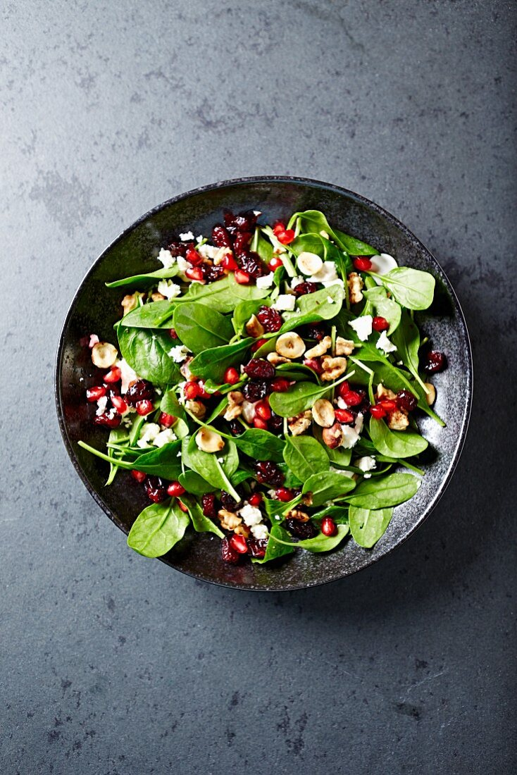 Spinach salad with dried cranberries, pomegranate seeds and toasted nuts