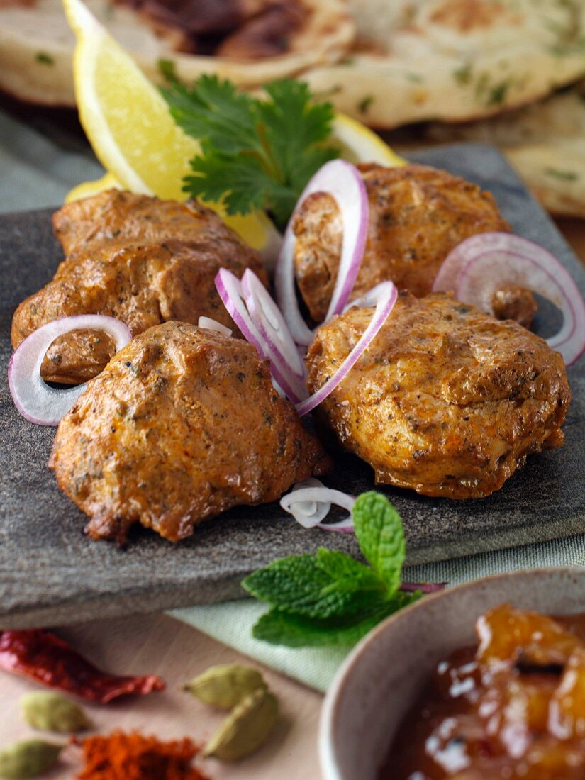 Chicken tikka with red onion slices and spices