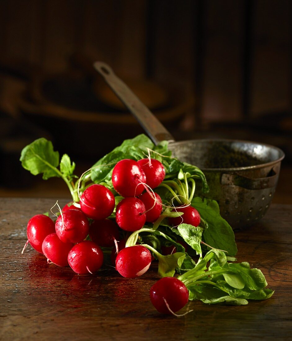 Radishes in front of an old kitchen sieve