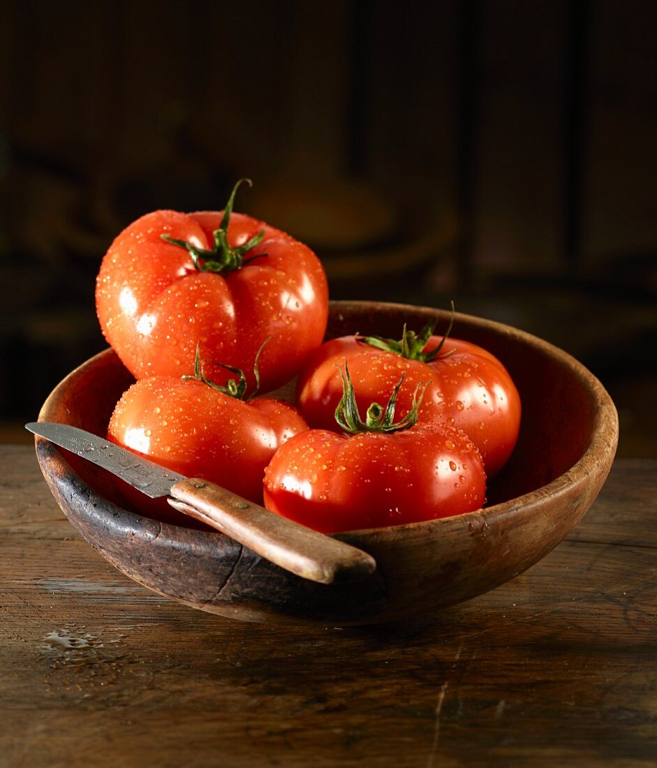 Tomatoes with drops of water and a knife in a wooden bowl