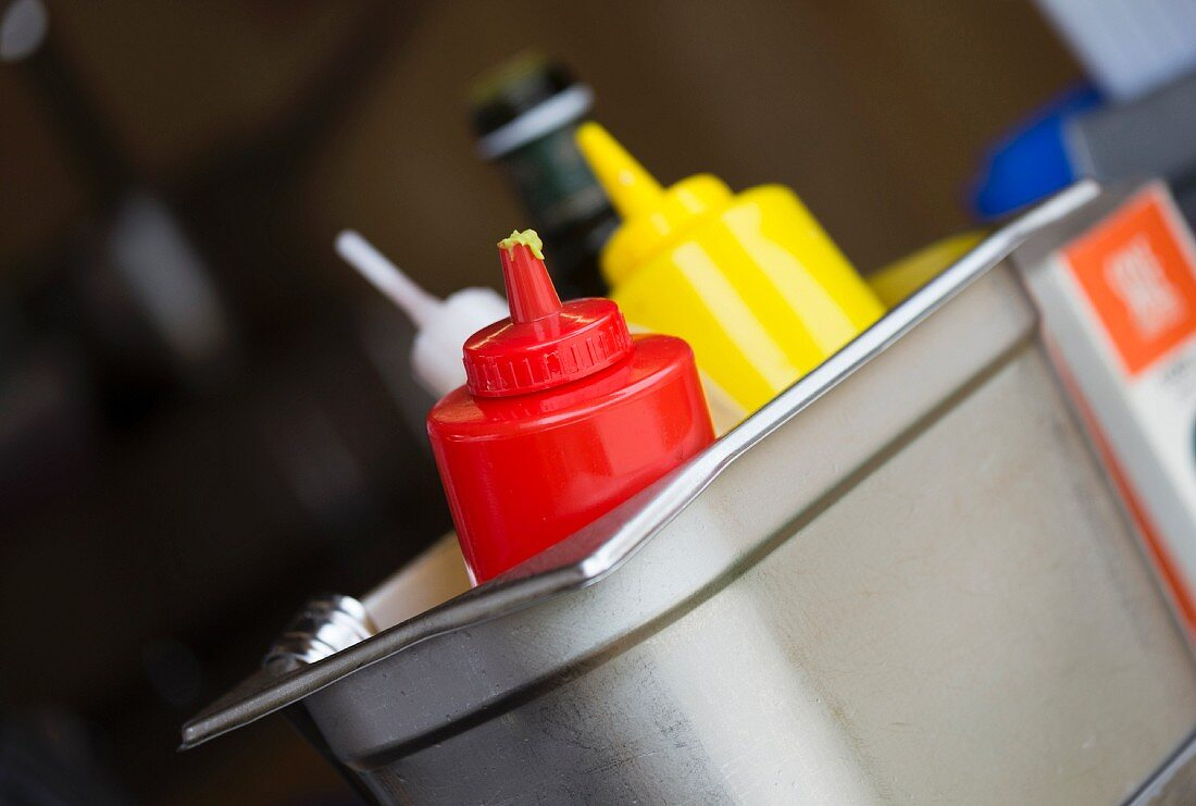 Ketchup, mustard and seasoning sauces in a metal container in a restaurant