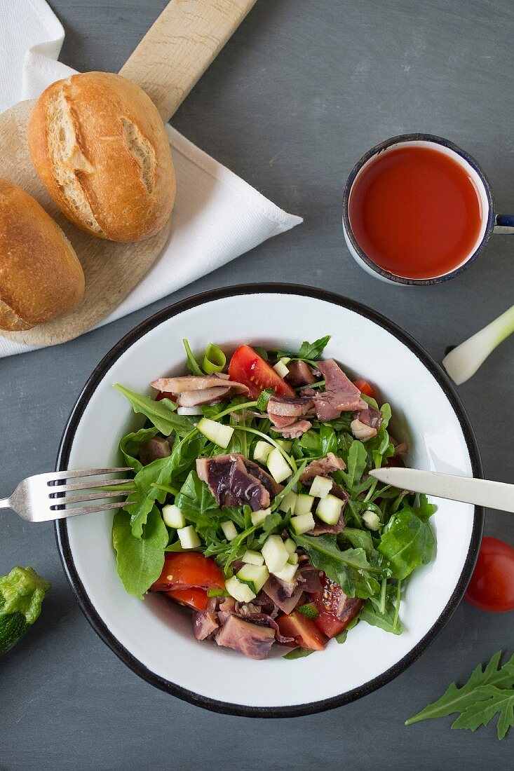 Seafood salad served with crusty bread rolls and cherry juice (seen from above)