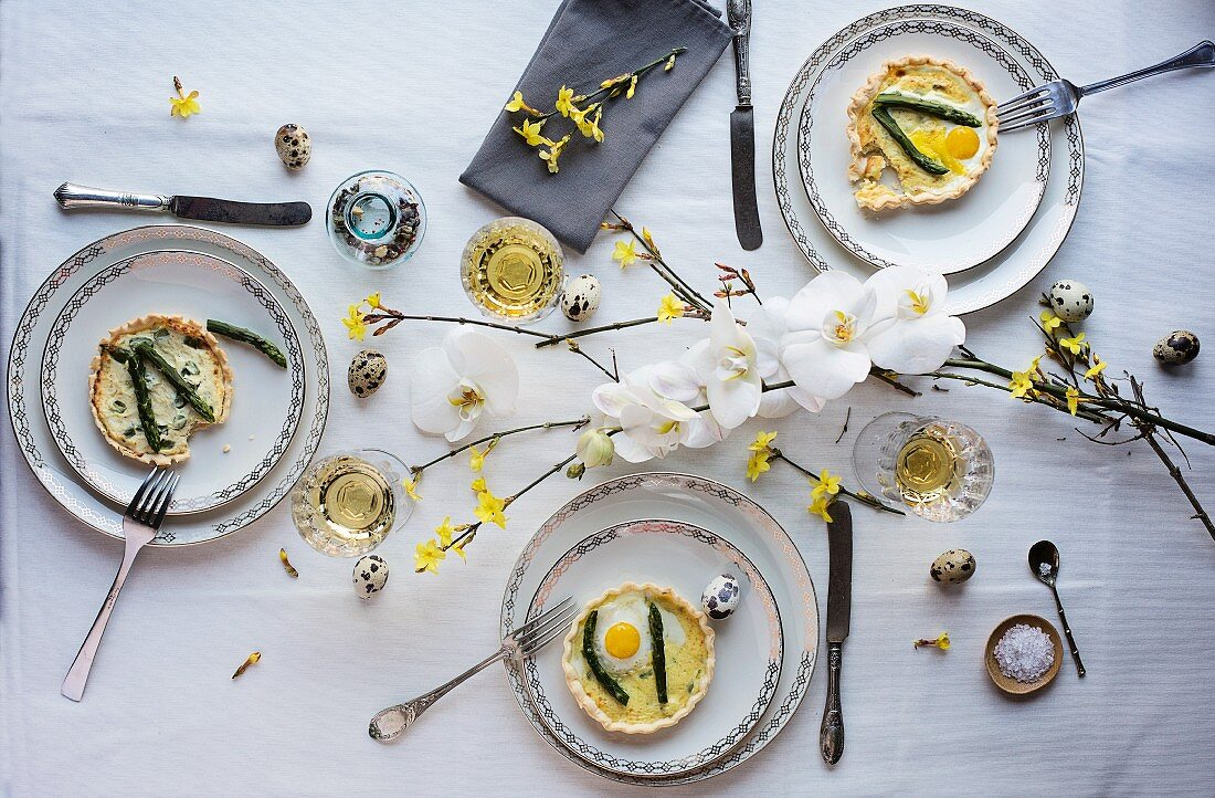Asparagus quiche with fried quail egg on a dining table set for Easter