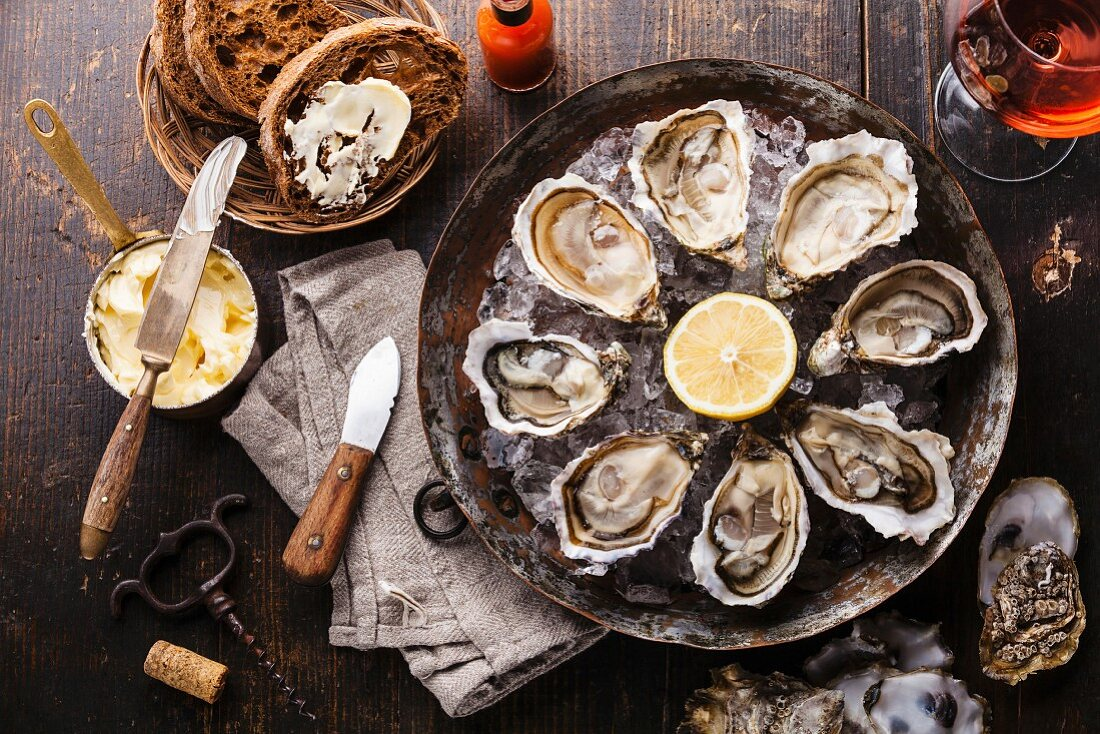 Opened Oysters on metal copper plate with dark bread with butter and rose wine on dark wooden background