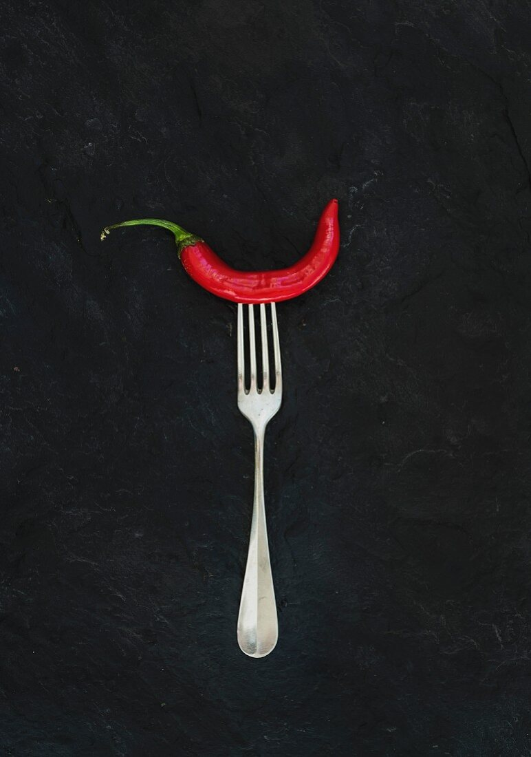 Red hot chili pepper on vintage silver fork over black slate stone background, top view