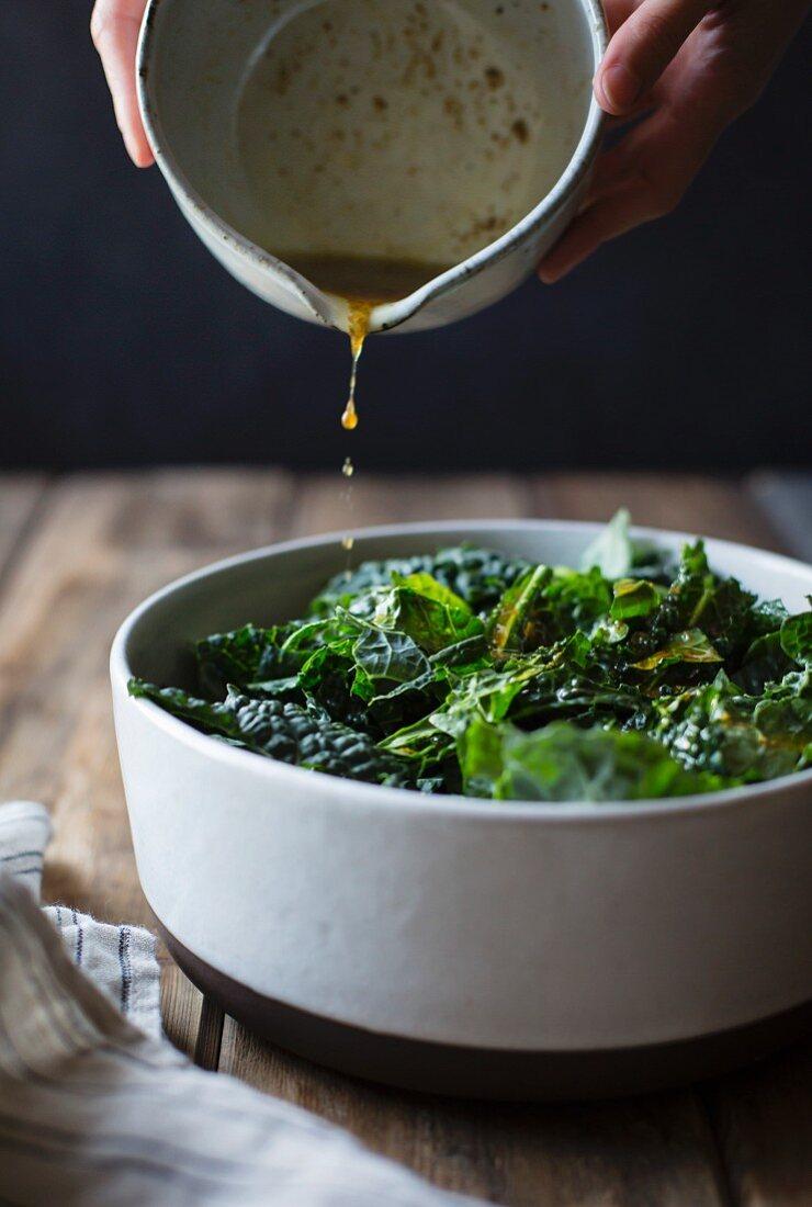 Pouring salad dressing over kale