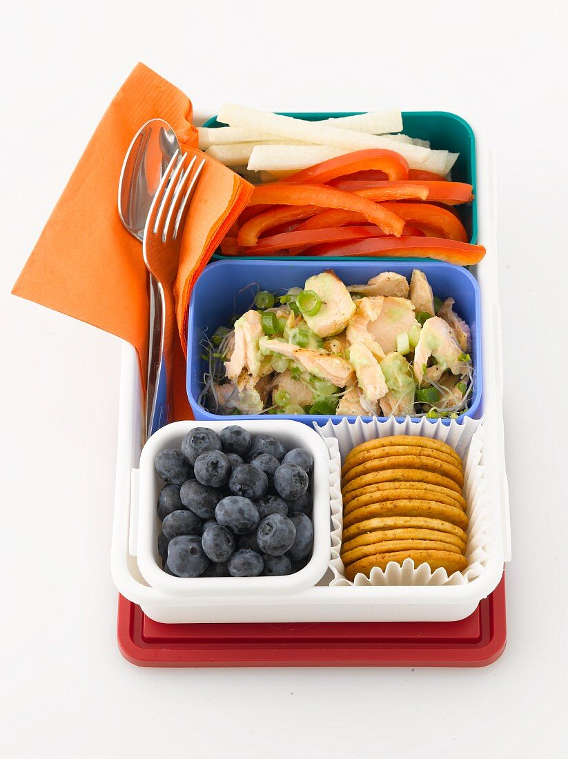 A packed lunch with chicken, vegetables, blueberries and crackers