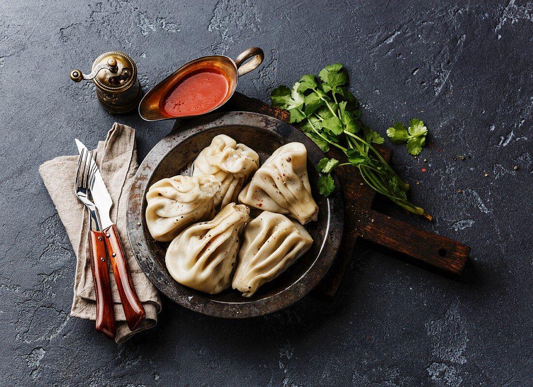 Georgian dumplings Khinkali with meat and tomato spicy sauce satsebeli on dark stone background