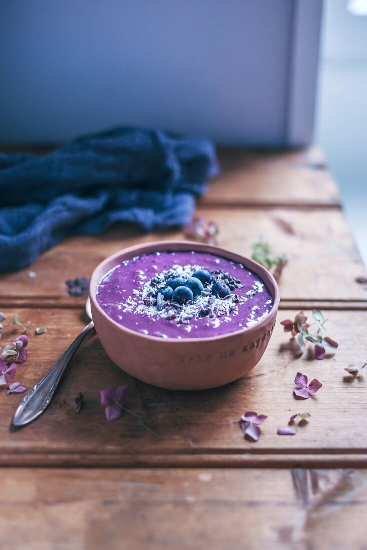 Blueberry acai smoothie bowl topped with blueberries, shredded coconut and cacao nibs on rustic wooden table