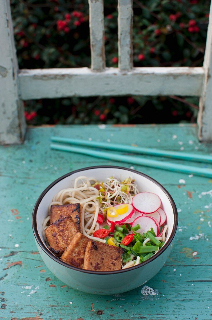 A bowl of traditional Japanese soup ramen served with tofu, slices of radish, chopped spring onion, fresh sprouts and sliced chili