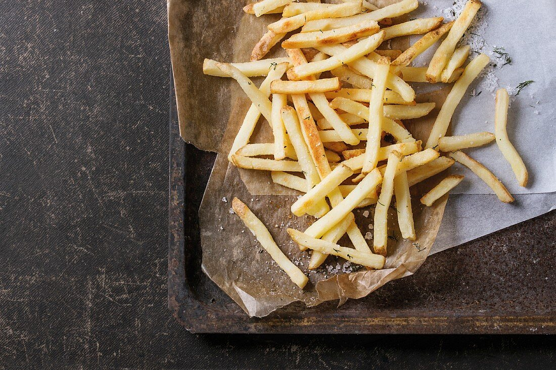 Fast food french fries potatoes with skin served with salt and herbs on baking paper on old rusty oven tray