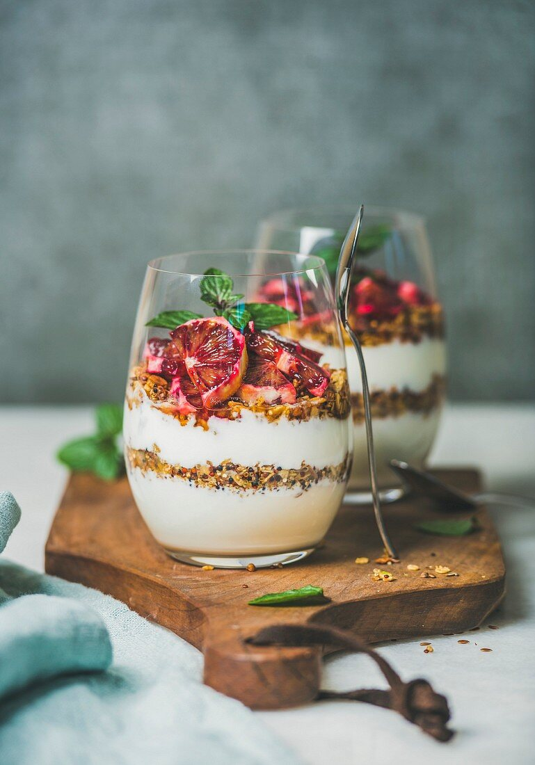 Healthy breakfast. Greek yogurt, granola, blood orange layered parfait in glasses with fresh mint