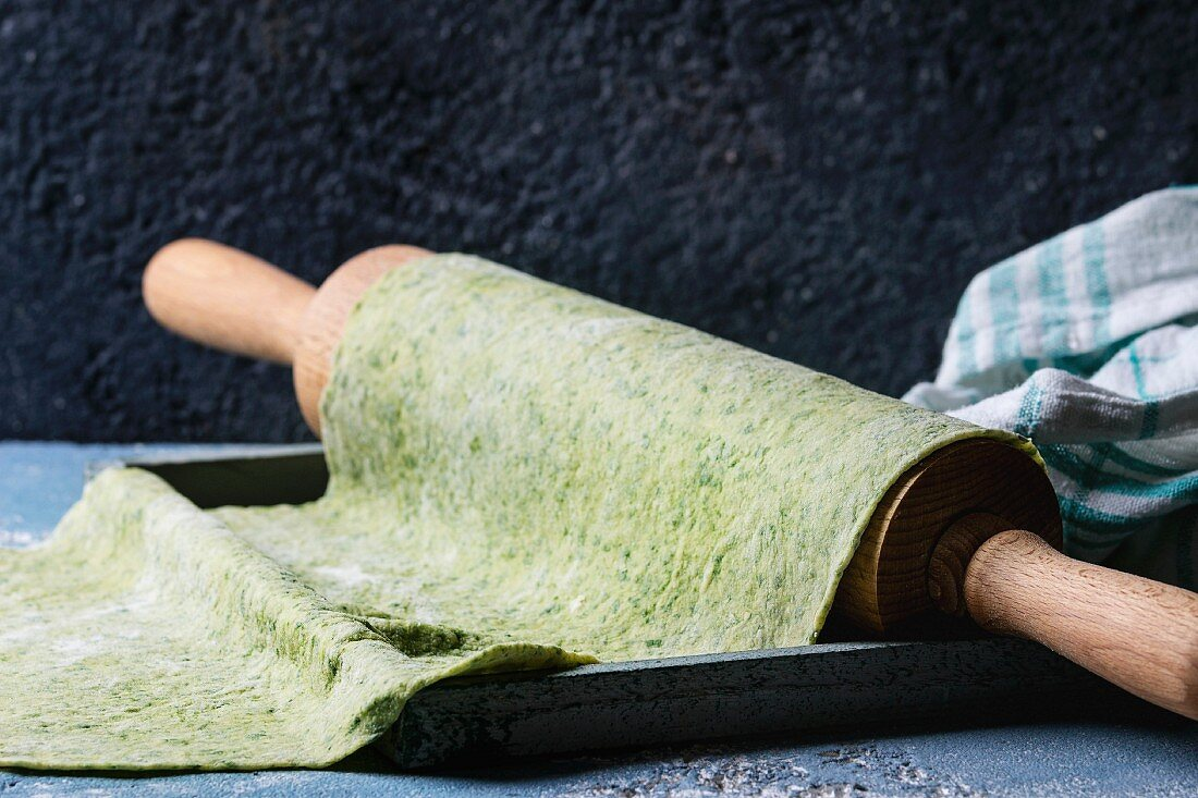 Fresh homemade green spinach rolled dough for pasta tagliatelle on wood rolling pin