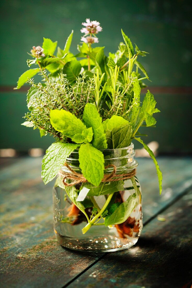 Fresh italian herbs in water on rustic background