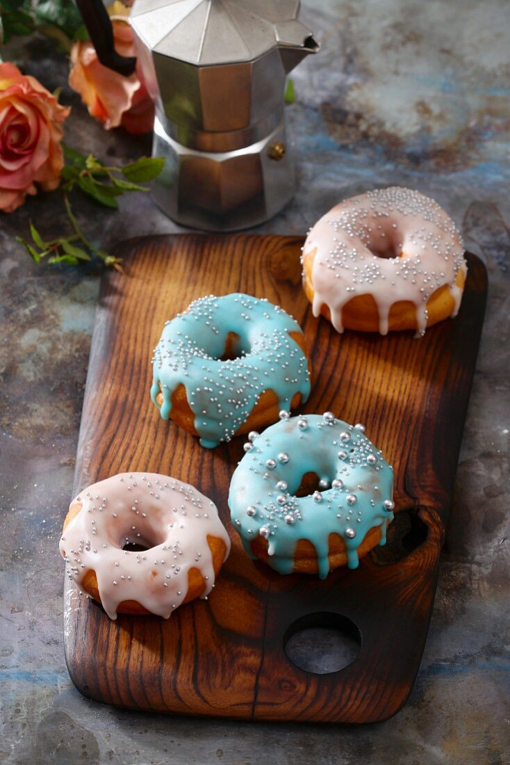 Doughnuts with colourful icing and silver sugar beads