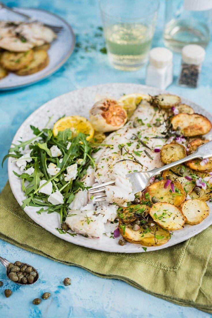 Oven-baked Barramundi fish fillet with crispy potatoes and rocket salad