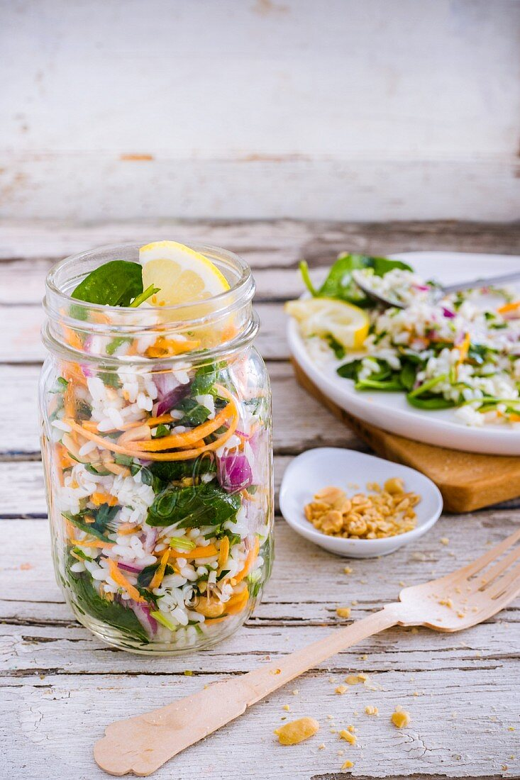 Rice salad with baby leaf spinach, carrot, red onion, lemon vinaigrette and peanuts in a glass