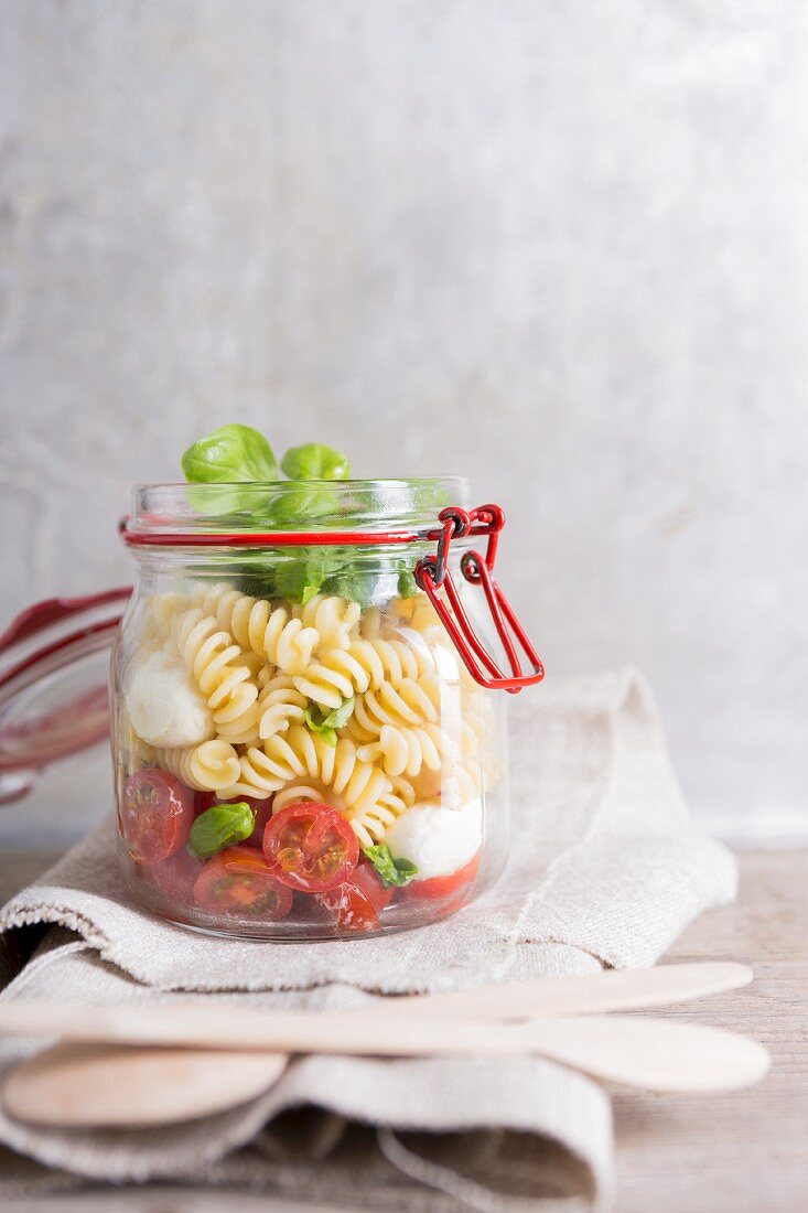 Pasta salad with tomatoes, mozzarella and basil in a glass jar