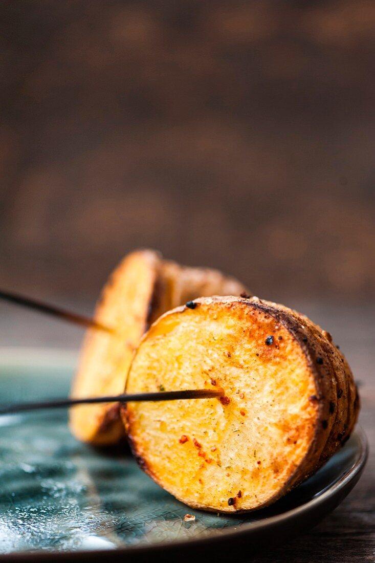 Hasselback potato halves on skewers