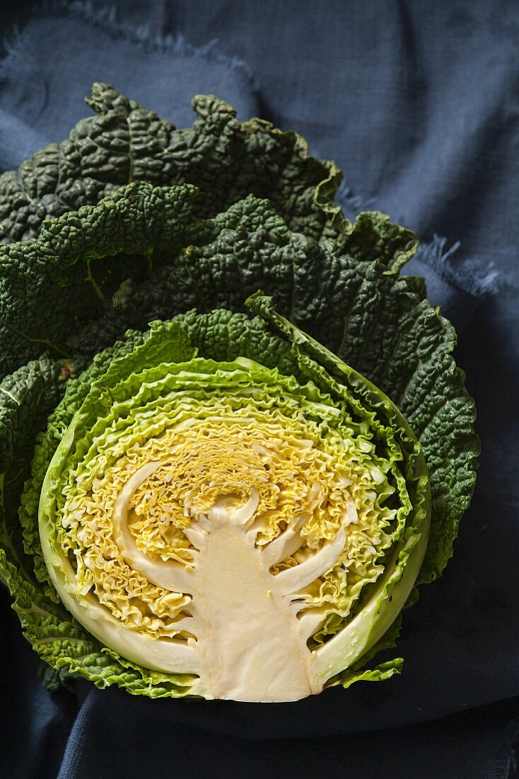 Savoy cabbage cut in half showing the cross section on blue fabric
