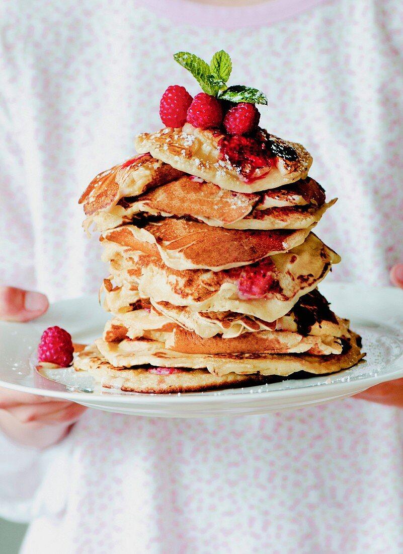 Gestapelte hausgemachte Vanille-Himbeer-Pancakes auf weißem Teller