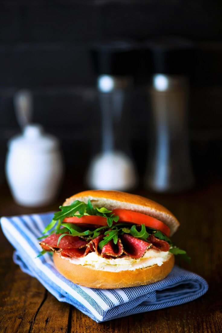 A bagel with cream cheese, pepper salami, rocket and tomatoes