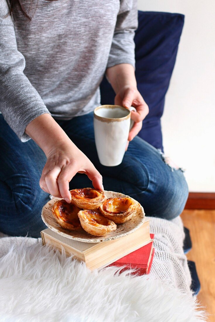 Female serving portuguese custard tarts with a cup of coffee