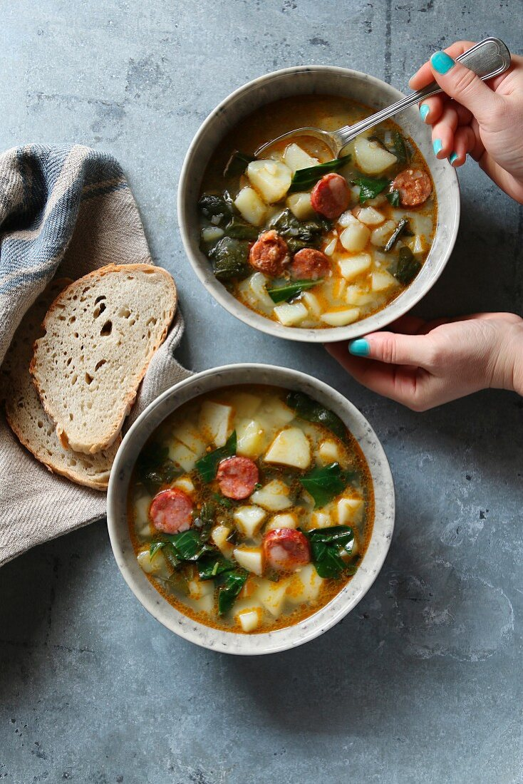Female hands holding a plate with sausage, kale and potato soup