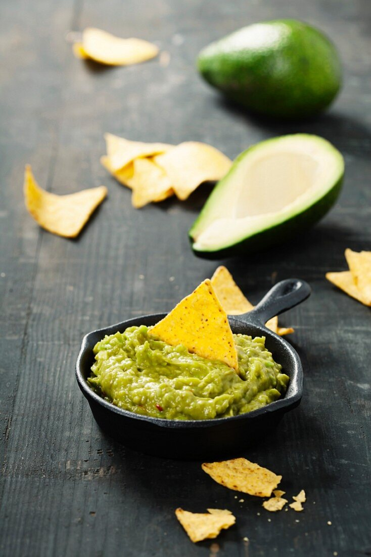 Mexican nachos chips with homemade fresh guacomole sauce over old background