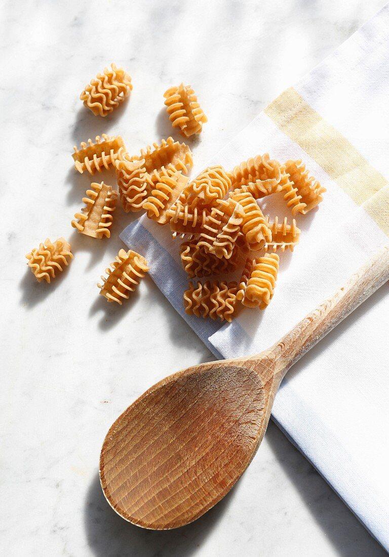 Pasta (radiatori, armoniche) and a wooden spoon