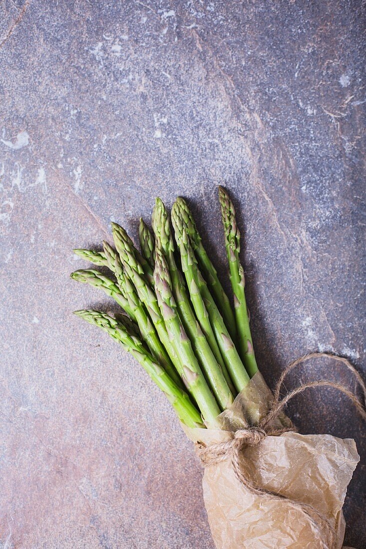 A bunch of fresh asparagus spears in a paper bag tied with string