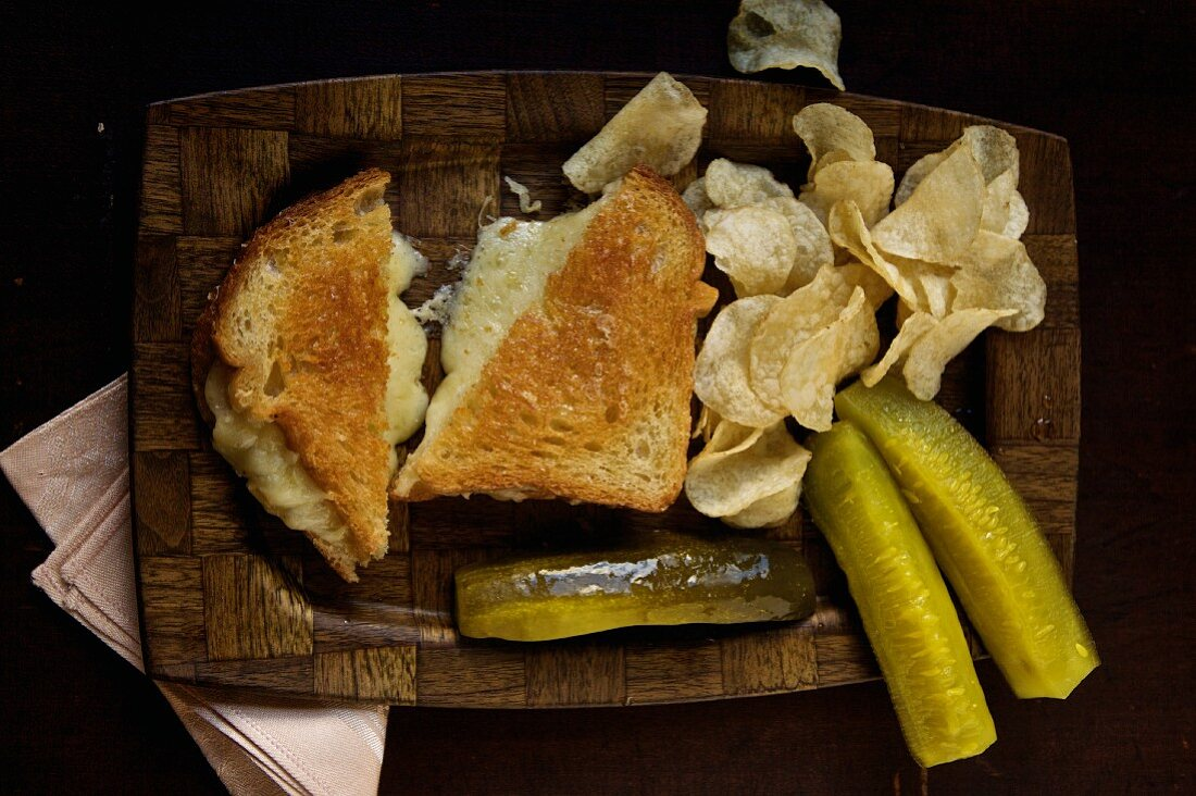 Grilled cheese sandwich with chips and pickles