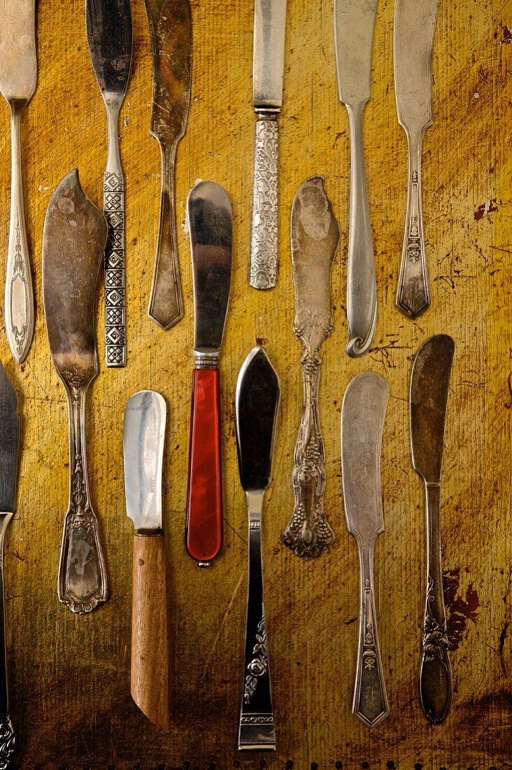 Selection of antique butter knives on a rustic board