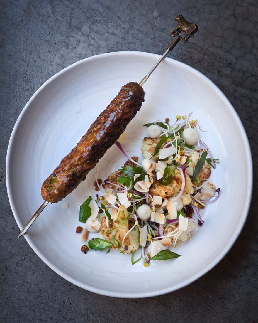 A minced lamb skewer with cauliflower and coconut salad