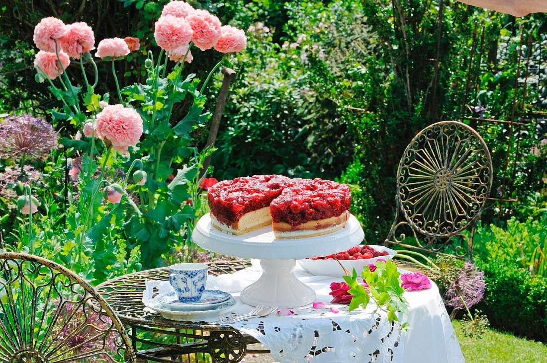 Raspberry cake on a cake stand in a summer garden