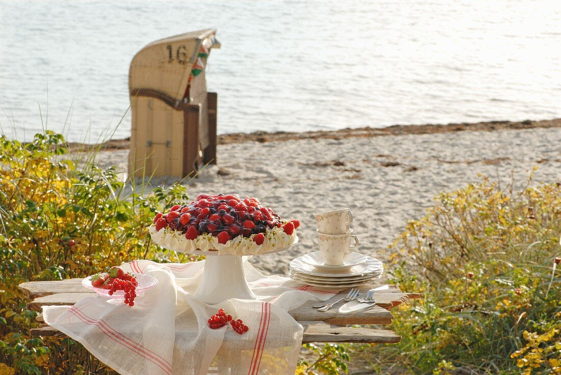 Summer berry cake on a wooden bench on the beach