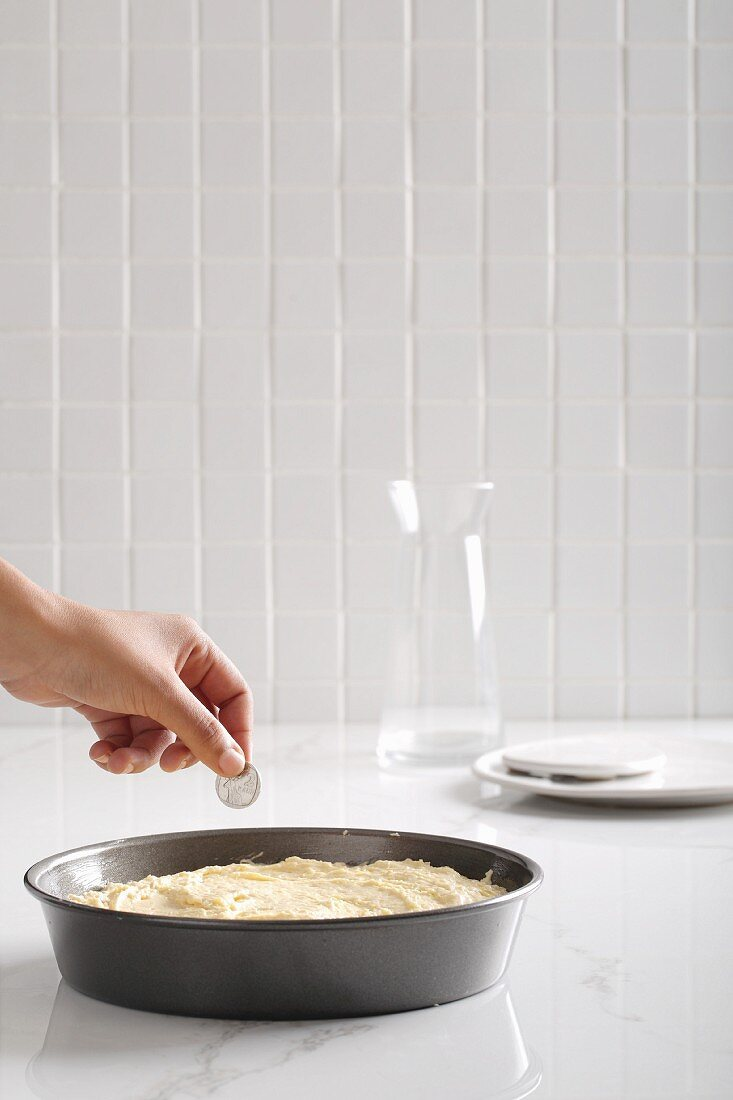 A hand putting a coin into an unbaked cake