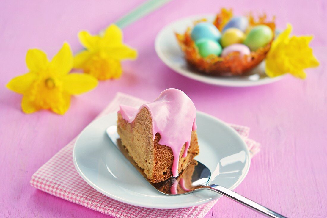 A piece of gugelhupf with a pink sugar glaze, a caramel nest with colourful sugar eggs and daffodils in the background