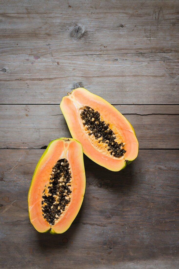 Halved papaya fruit on a wooden table