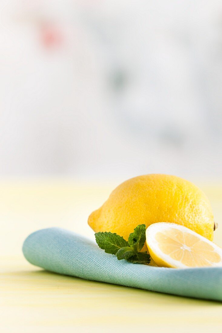 Ganze Zitrone, Zitronenscheibe und Minze