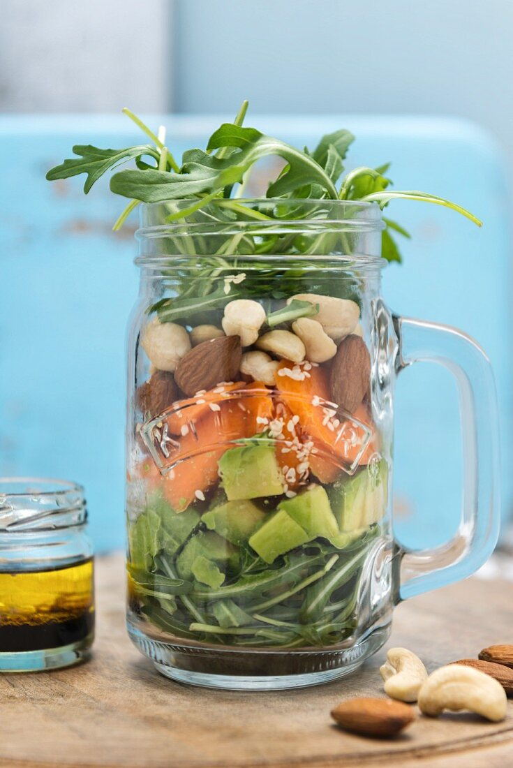 Vegan avocado and sweet potato salad with cashews and rocket in a glass jar