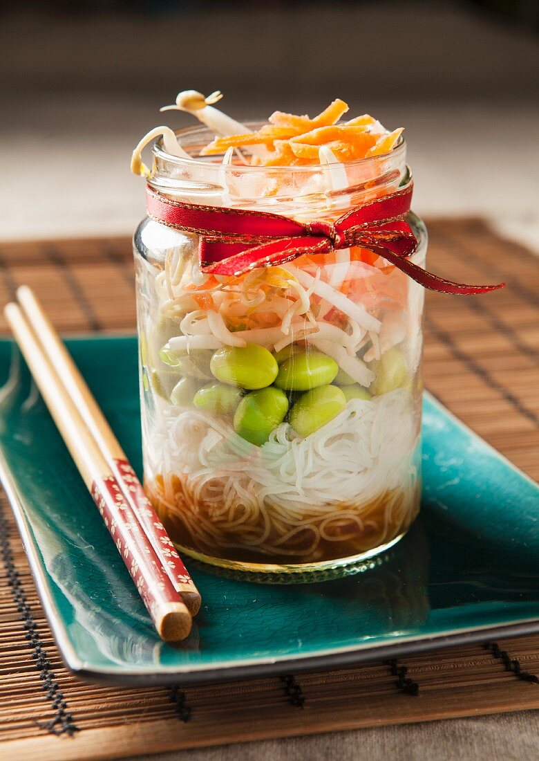 Edamame bean salad in a trendy lunch jar with chopsticks on a teal plate and bamboo mat