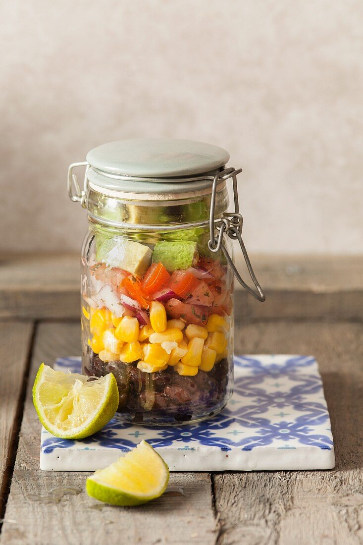 South Western Style bean salad lunch jar on a ceramic tile with lime wedges and stone back ground
