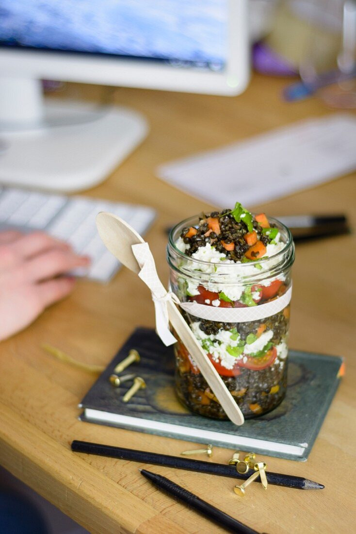 Lentil salad with carrots, tomatoes and feta in a glass jar, at an office