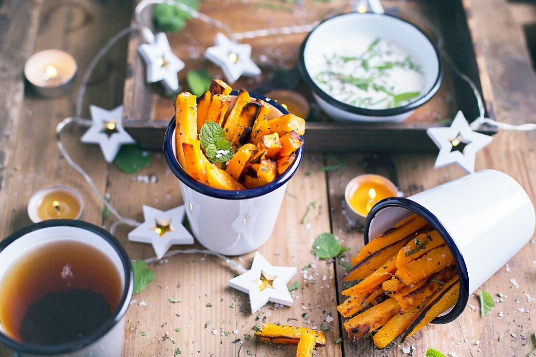 Sweet Potatoes Fries with sae salt flakes and fresh mint leaves; served on a wooden table